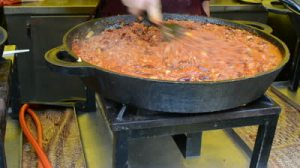 stock-footage-hand-with-tool-mix-slumgullion-meal-cooked-in-big-pot-in-outdoor-street-fair